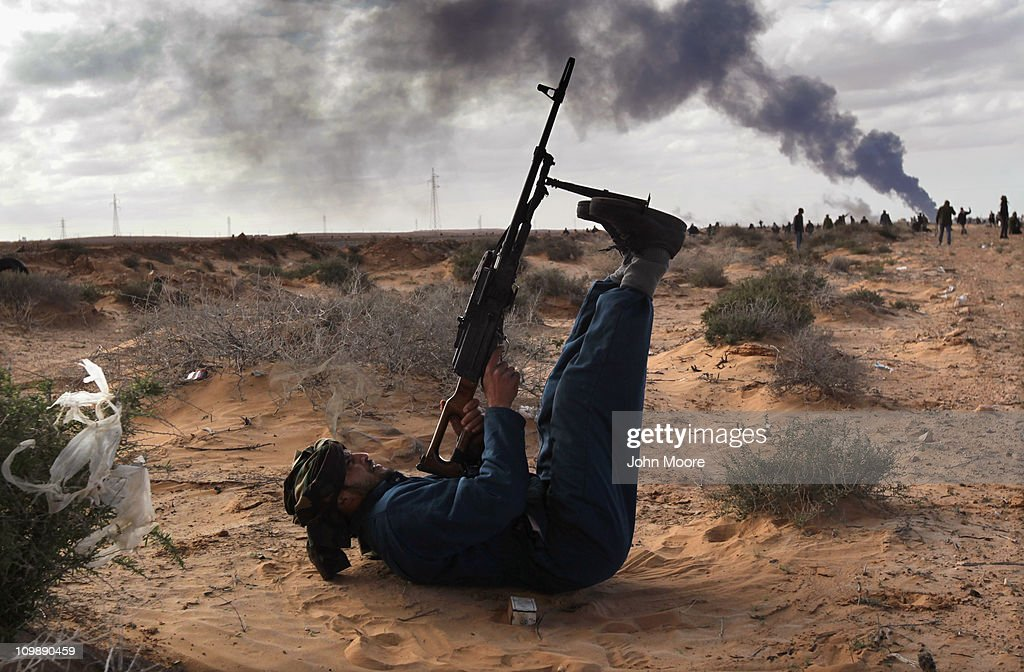 A Libyan rebel fires on a government jet as a facility burns on the frontline on March 9, 2011 near Ras Lanuf, Libya. The rebels pushed back government troops loyal to Libyan leader Muammar Gaddafi towards Ben Jawat.