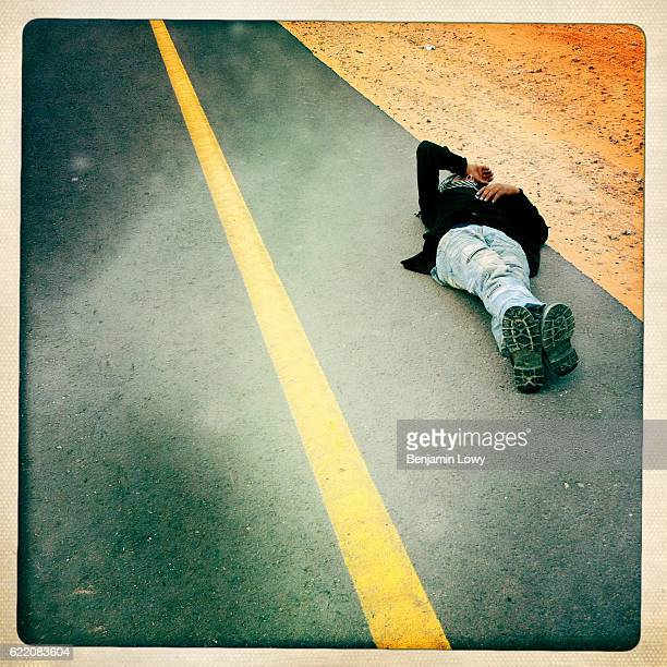 Libyan rebel lies on the road in frustration following a massive retreat in the face of relentless mortar attacks on March 29 2011 in Bin Jawad Libya