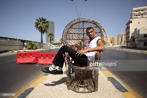 A Libyan rebel sits on a bamboo chair at a checkpoint in the capital Tripoli on August 31 as rebel forces set up a security belt around the city...
