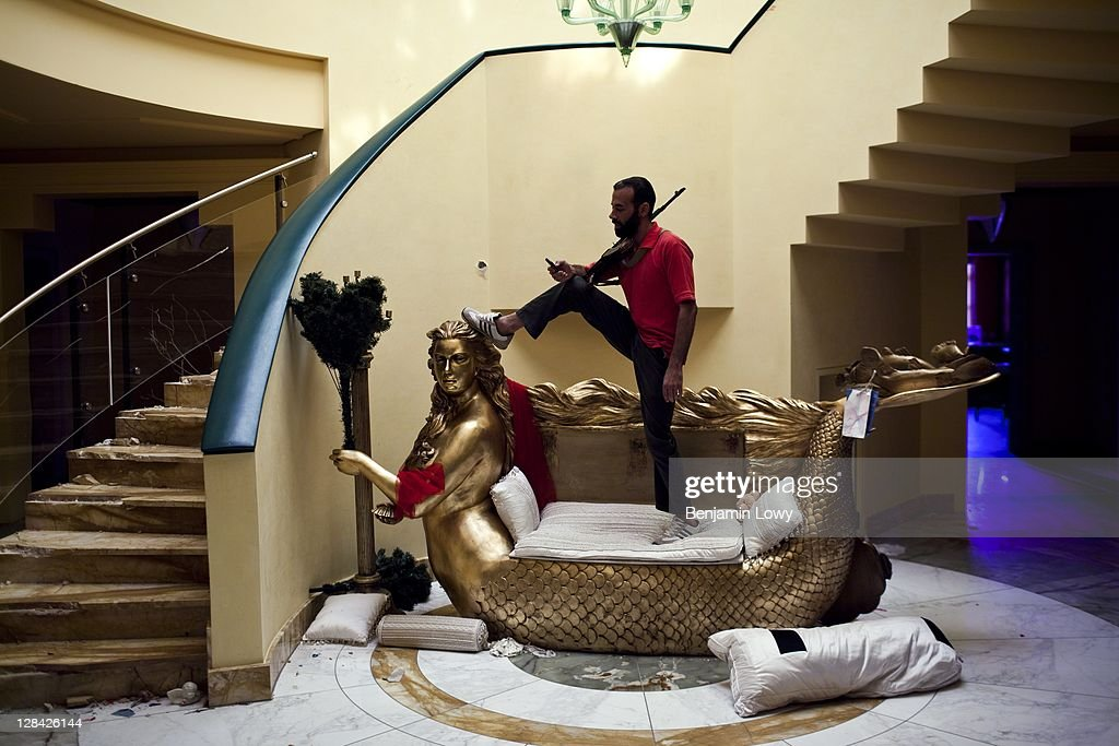 A Libyan Rebel stands and posed on an ornate mermaid loveseat, a wedding gift made to resemble Aisha Gaddafi, daughter of former Libyan dictator Moammar Gaddafi, while guarding Aisha's home from looters, on August 29, 2011 in Tripoli, Libya.