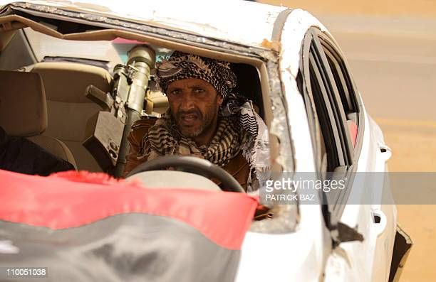 A Libyan rebel with a SAM7 sitting on the backseat drives a wrecked car in Ajdabiya on March 14 2011 as Libyan strongman Moamer Kadhafi's forces...