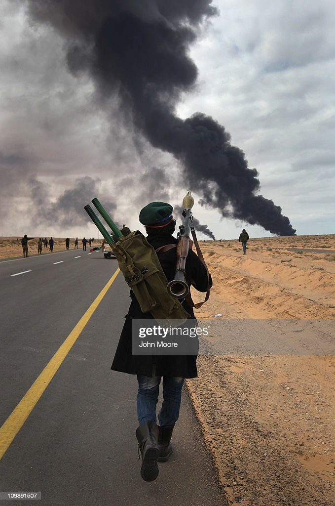 Libyan rebels advance during a battle with government troops as a facility burns on the frontline on March 9, 2011 near Ras Lanuf, Libya. The rebels pushed back government troops loyal to Libyan leader Muammar Gaddafi towards Ben Jawat.