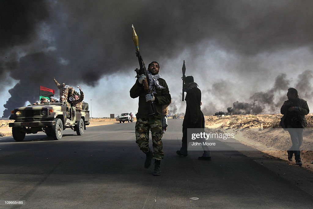 Libyan rebels battle government troops as smoke from a damaged oil facility darkens the frontline sky on March 11, 2011 in Ras Lanuf, Libya. Government troops loyal to Libyan leader Muammar Gaddafi drove opposition forces out of the strategic oil town, forcing a frantic rebel retreat through the desert.