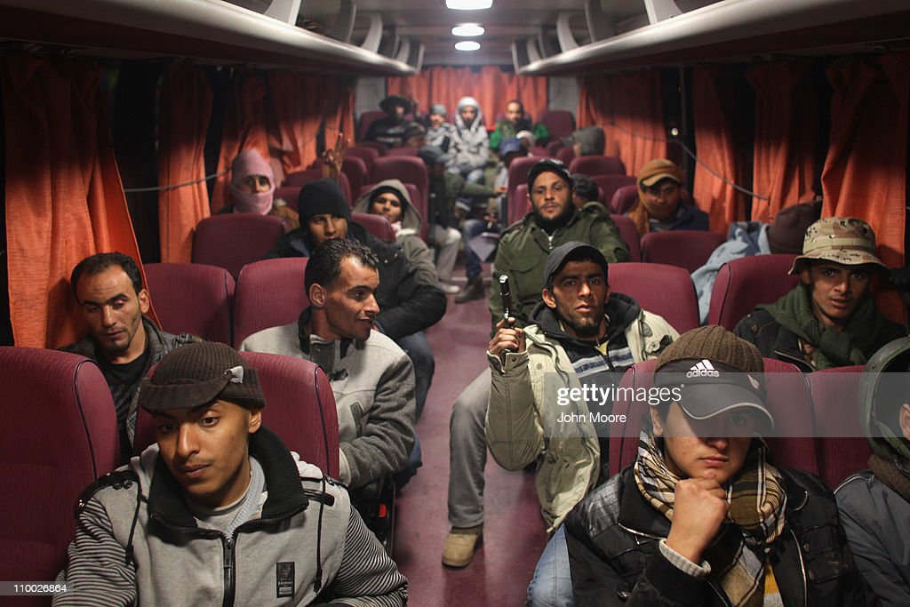 Libyan rebels board a bus to take them away from the frontline on March 12, 2011 near Brega, Libya. Opposition forces have been losing ground as government troops loyal to Libyan leader Muammar Gaddafi press a counter-offensive to the east.