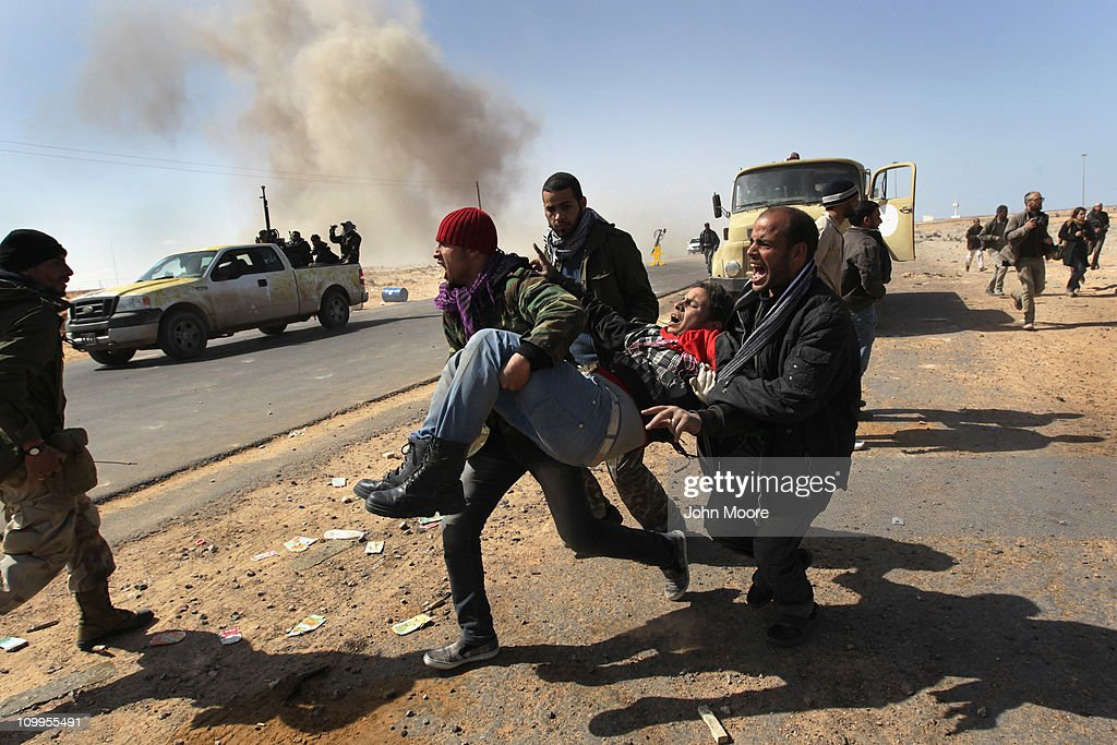Libyan rebels carry a comrade wounded in a government airstrike on the frontline on March 11, 2011 in Ras Lanuf, Libya. Government troops loyal to Libyan leader Muammar Gaddafi drove opposition forces out of the strategic oil town, forcing a frantic rebel retreat through the desert.