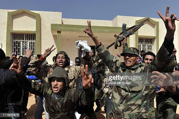 Libyan rebels celebrate outside deserted government offices in the village of Harawa as they advance towards Moamer Kadhafi's hometown of Sirte on...