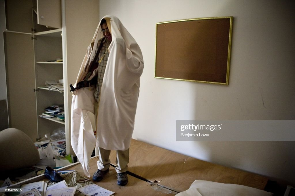 A Libyan rebels dresses in one of Gaddafi's robes while walking through the looted and NATO bombed home of former Libyan dictator Moammar Gaddafi's son Motasem, on September 2 2011 in Tripoli, Libya.