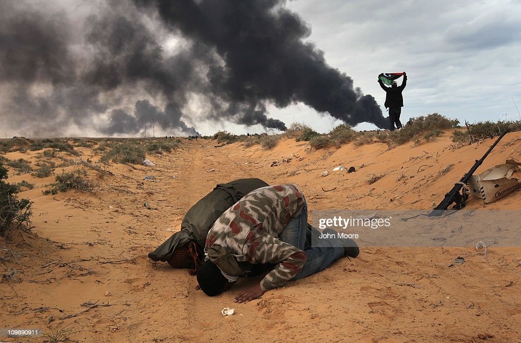 Libyan rebels pause to pray during a battle with government troops as a facility burns on the frontline on March 9, 2011 near Ras Lanuf, Libya. The rebels pushed back government troops loyal to Libyan leader Muammar Gaddafi towards Ben Jawat.