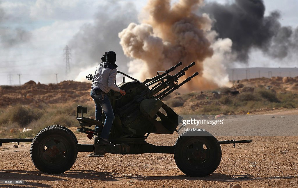 Libyan rebels retreat as government bombs explode around them on the frontline on March 6, 2011 near Ben Jawat, Libya. Rebels lost territory as forces loyal to Libyan leader Muammar Gaddafi pushed them back to the town of Ras Lanuf.