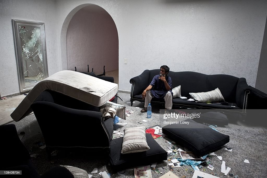 A Libyan rebels sits on a couch and smokes a cigarette in the looted and NATO bombed home of former Libyan dictator Moammar Gaddafi's son Motasem, on September 2 2011 in Tripoli, Libya.