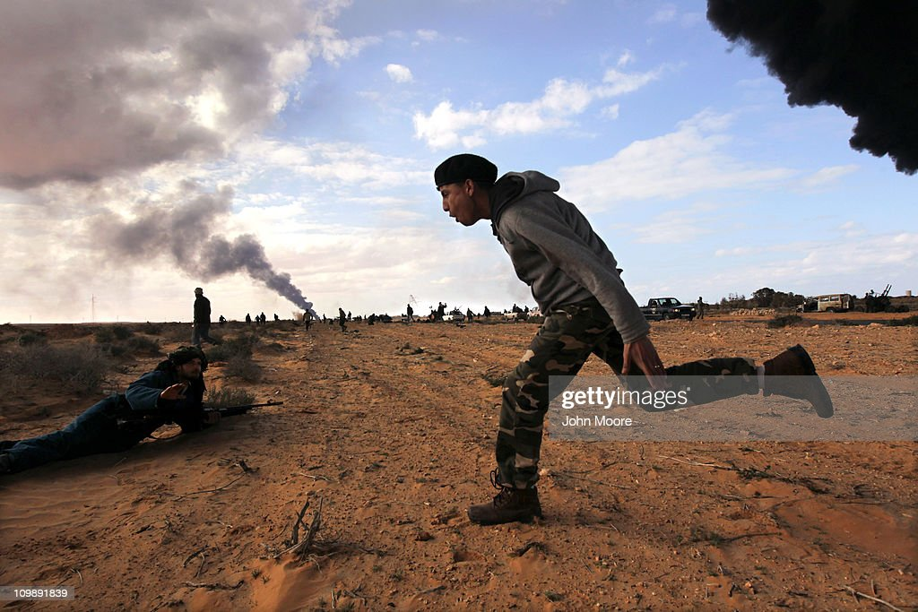 Libyan rebels take cover during a battle with government troops as a facility burns on the frontline on March 9, 2011 near Ras Lanuf, Libya. The rebels pushed back government troops loyal to Libyan leader Muammar Gaddafi towards Ben Jawat.