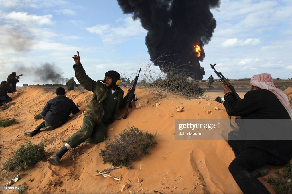 Libyan rebels take positions while fighting government troops as a facility burns on the frontline on March 9, 2011 near Ras Lanuf, Libya. The rebels pushed back government troops loyal to Libyan leader Muammar Gaddafi towards Ben Jawat.