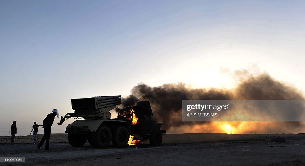 Libyan rebels walk past a burning multirocket launcher at sunset outside the oil rich town of Ras Lanuf on March 27 2011 as rebels press on as far as...
