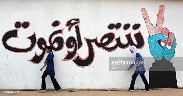 Libyan schoolgirls run past graffiti reading 'We win or die' at a school in Benghazi on October 6 2011 The clapping of hands the stamping of feet and...