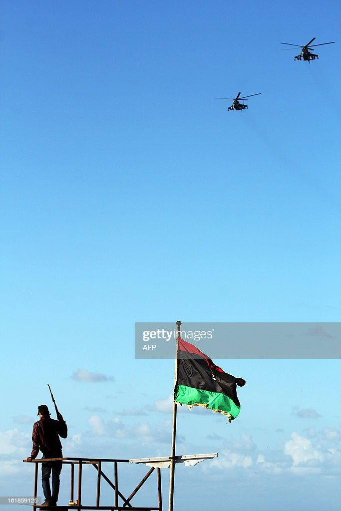 A Libyan security force member stands on top of a watch tower as hundreds of Libyans arrive to celebrate the second anniversary of the Libyan uprising in Tahrir Square on February 17, 2013, in the eastern city of Benghazi. Security forces were on high alert across Libya as the north African nation marked two years since the start of the revolt that toppled Moamer Kadhafi after four decades of iron rule. The anniversary of the uprising that ended with Kadhafi's killing in October 2011 comes as Libya's new rulers battle critics calling for a 'new revolution' and accusing them of failing to usher in much-needed reforms.
