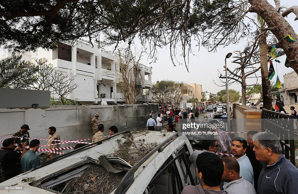 Libyan security forces and civilians gather outside the French embassy building (L) in Tripoli following a car bomb attack, on April 23, 2013. A car bomb blasted the embassy of France in Tripoli, injuring two French guards and causing serious damage to the building, embassy and Libyan sources said. AFP PHOTO/MAHMUD TURKIA