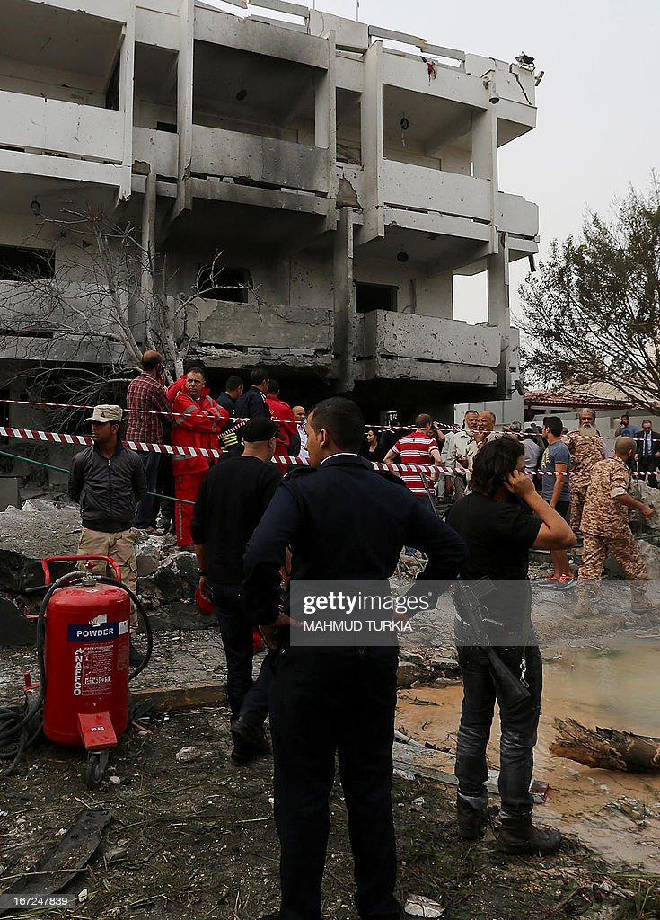 Libyan security forces gather in front of the French embassy building in Tripoli following a car bomb attack, on April 23, 2013. A car bomb blasted the embassy of France in Tripoli, injuring two French guards and causing serious damage to the building, embassy and Libyan sources said. AFP PHOTO/MAHMUD TURKIA