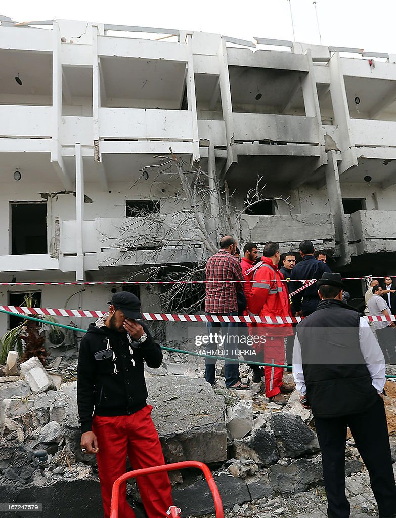 Libyan security forces gather outside the French embassy building in Tripoli following a car bomb blast, on April 23, 2013. A car bomb blasted the embassy of France in Tripoli, injuring two French guards and causing serious damage to the building, embassy and Libyan sources said. AFP PHOTO/MAHMUD TURKIA