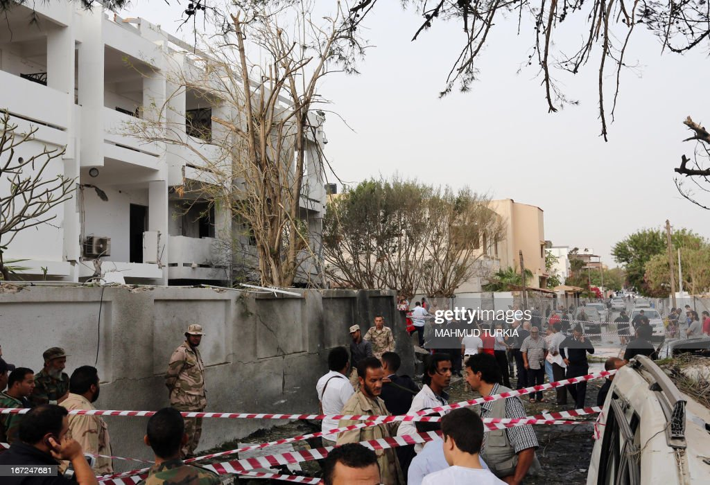 Libyan security forces gather outside the French embassy building (L) in Tripoli following a car bomb attack, on April 23, 2013. A car bomb blasted the embassy of France in Tripoli, injuring two French guards and causing serious damage to the building, embassy and Libyan sources said. AFP PHOTO/MAHMUD TURKIA
