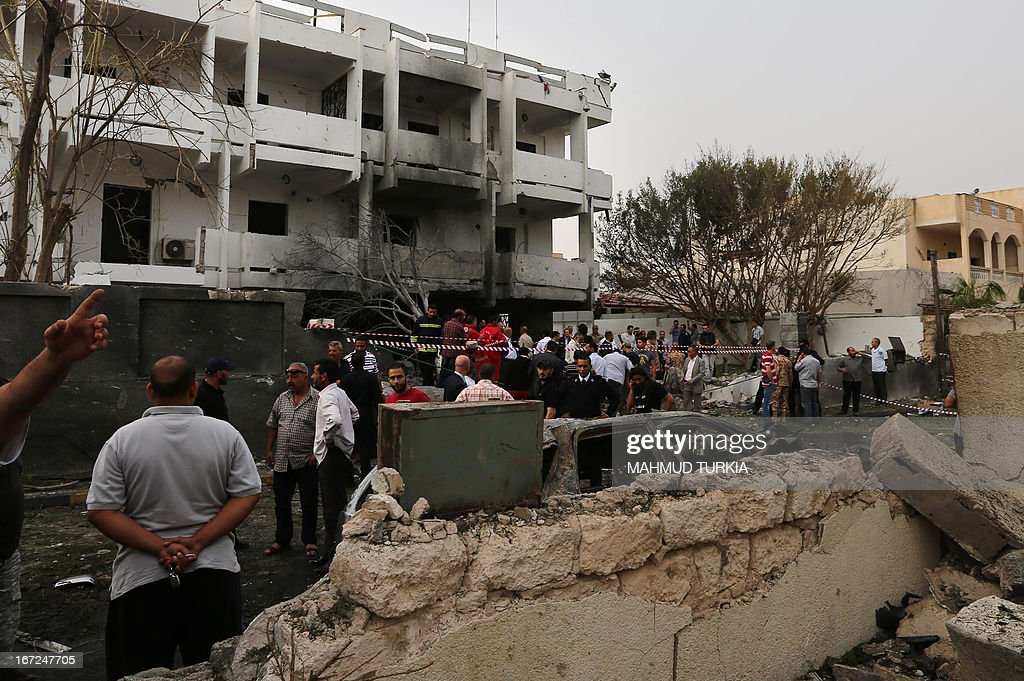 Libyan security forces gather outside the French embassy building in Tripoli following a car bomb attack, on April 23, 2013. A car bomb blasted the embassy of France in Tripoli, injuring two French guards and causing serious damage to the building, embassy and Libyan sources said. AFP PHOTO/MAHMUD TURKIA