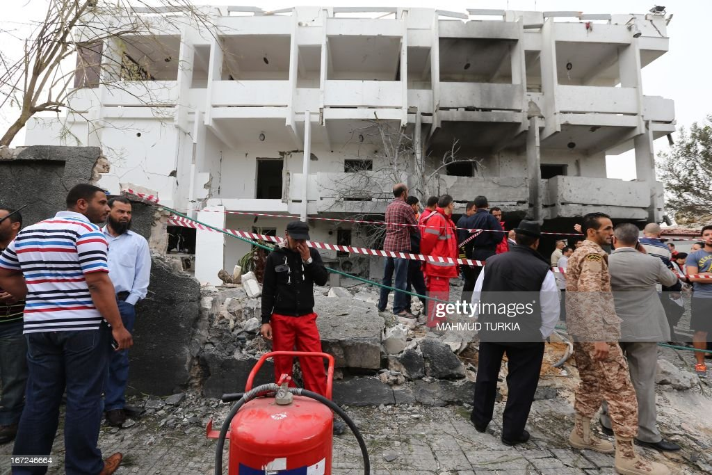 Libyan security forces gather outside the French embassy in Tripoli following a car bomb blast, on April 23, 2013. A car bomb blasted the embassy of France in Tripoli, injuring two French guards and causing serious damage to the building, embassy and Libyan sources said. AFP PHOTO/MAHMUD TURKIA