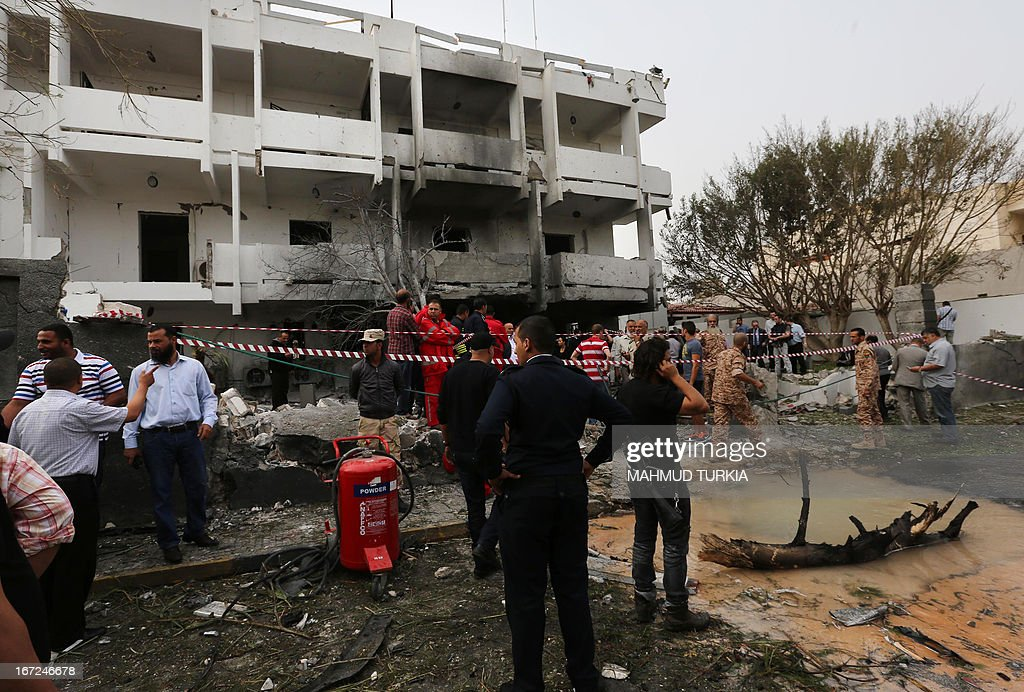 Libyan security forces gather outside the French embassy in Tripoli following a car bomb blast, on April 23, 2013. A car bomb blasted the embassy of France in Tripoli, injuring two French guards and causing serious damage to the building, embassy and Libyan sources said.