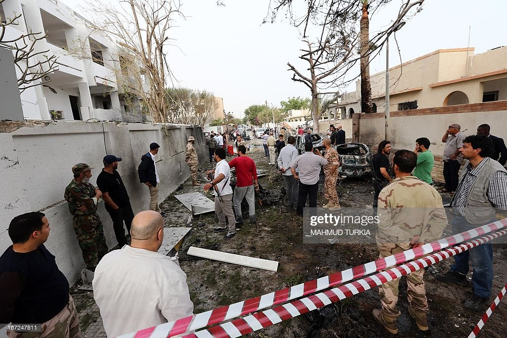 Libyan security forces gather outside the French embassy (L) in Tripoli following a car bomb blast, on April 23, 2013. A car bomb blasted the embassy of France in Tripoli, injuring two French guards and causing serious damage to the building, embassy and Libyan sources said. AFP PHOTO/MAHMUD TURKIA