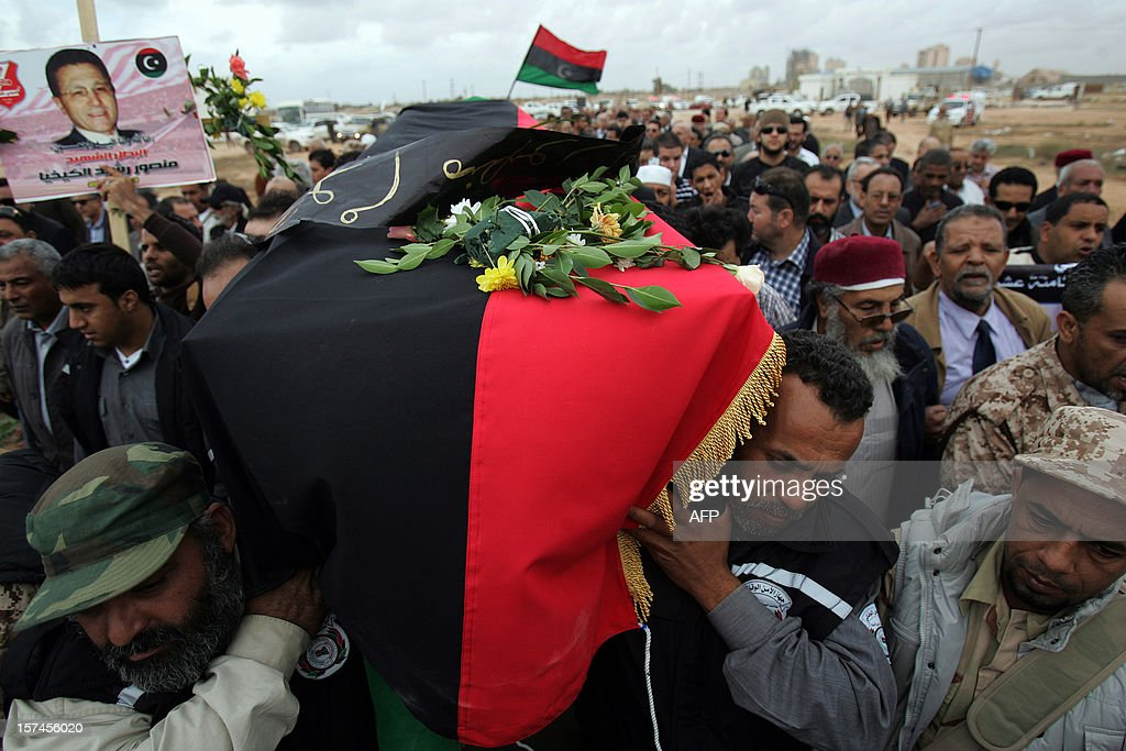 Libyan security staff carry the coffin of leading Libyan dissident Mansour al-Kikhia during his funeral procession in the eastern port city of Benghazi on December 3, 2012. Kikhia, who disappeared 19 years ago under the Kadhafi regime, was buried, weeks after his body was found in an intelligence services morgue, his brother said. AFP PHOTO / ABDULLAH DOMA