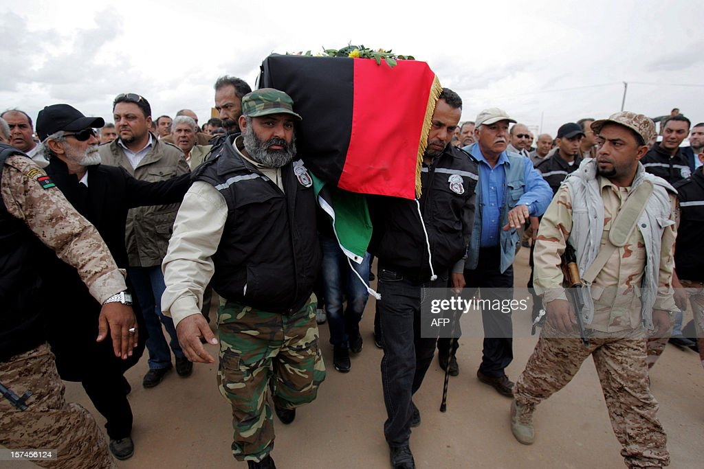 Libyan security staff carry the coffin of leading Libyan dissident Mansour al-Kikhia during his funeral procession in the eastern port city of Benghazi on December 3, 2012. Kikhia, who disappeared 19 years ago under the Kadhafi regime, was buried, weeks after his body was found in an intelligence services morgue, his brother said.