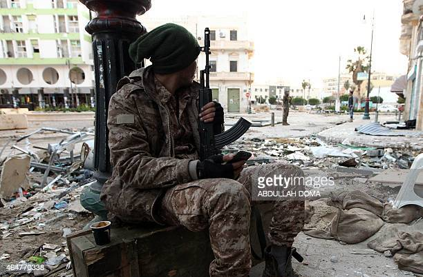 A Libyan soldier loyal to Libya's internationally recognised government of Abdullah alThani and General Khalifa Haftar rests on a sidewalk in the...