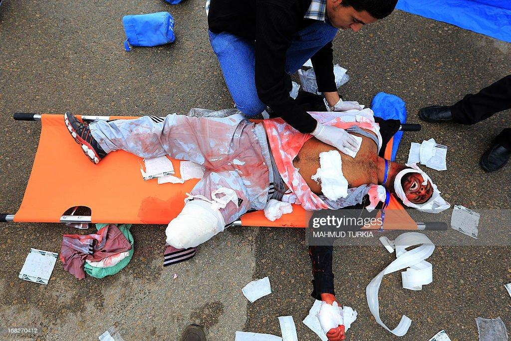 A Libyan volunteer screams while receiving medical attention during a drill simulating a plane crash organized by the International Committee of the Red Cross in cooperation with the Libyan Red Crescent, for training on disaster management at Mitiga Airport on December 12, 2012 in Tripoli.