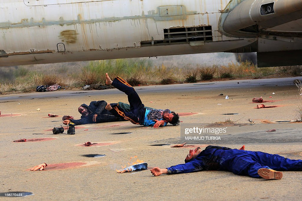 Libyan volunteers lay on the ground simulating a plane crash during a drill organized by the International Committee of the Red Cross in cooperation with the Libyan Red Crescent, for training on disaster management at Mitiga Airport on December 12, 2012 in Tripoli.