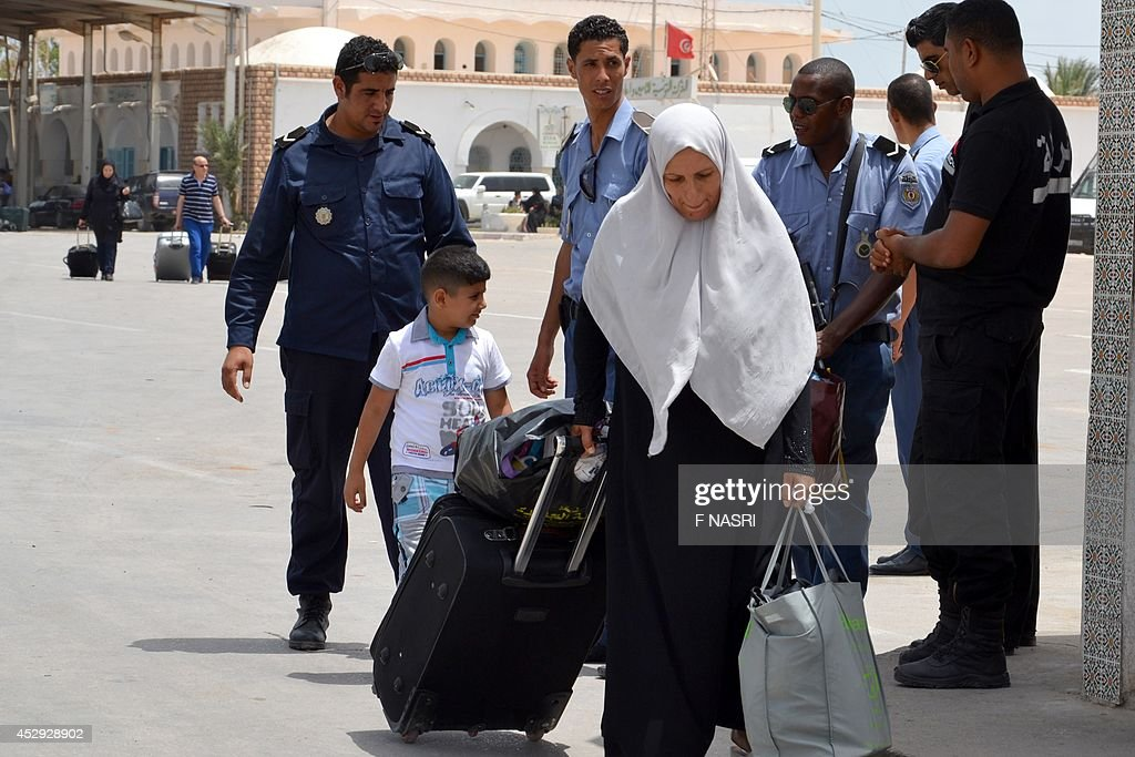 A Libyan woman fleeing the violence in her country enters Tunisia through the southern border crossing at Ras Jedir on July 30, 2014. Tunisia cannot cope with any massive influx of refugees who might seek to enter the country from strife-torn neighbouring Libya and will close its border if necessary, the foreign minister said. AFP PHOTO / F NASRI