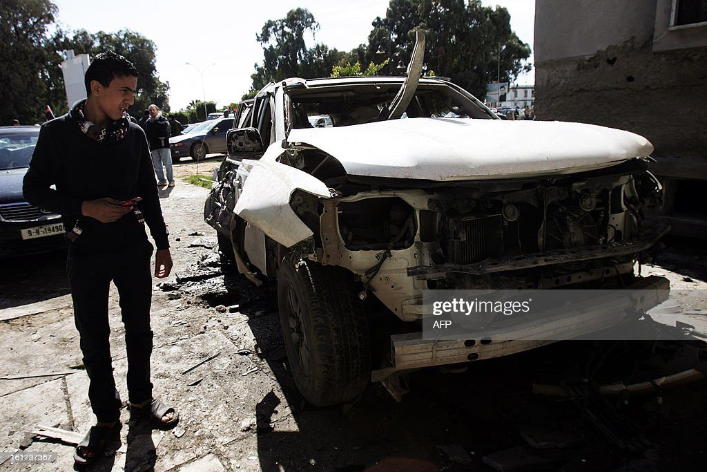 A Libyan youth stands next to the wreckage of an exploded car outside a police station on February 15, 2013 in the eastern Libyan city of Benghazi. Libya will mark at the end of the week the second anniversary of the uprising that toppled the regime of strongman Moamer Kadhafi, amid fears of fresh violence and calls for demonstrations across the country, with the government taking a series of measures to contain any attempt by supporters of the former regime to 'sow chaos'.