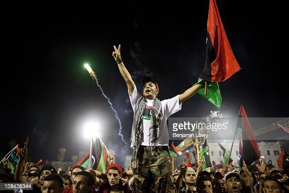 Libyans celebrate the fall of Libyan dictator Moammar Gaddafi in the the newly renamed Martyr's Square on August 30 2011 in Tripoli Libya