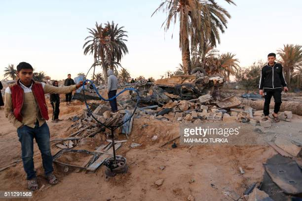 Libyans gather next to debris at the site of a jihadist training camp targeted in a US air strike near the Libyan city of Sabratha on February 19...