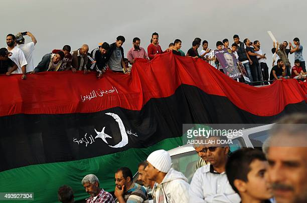 Libyans hold a large version of their national flag during a demonstration against a UNbrokered peace deal in the centre of the eastern coastal...