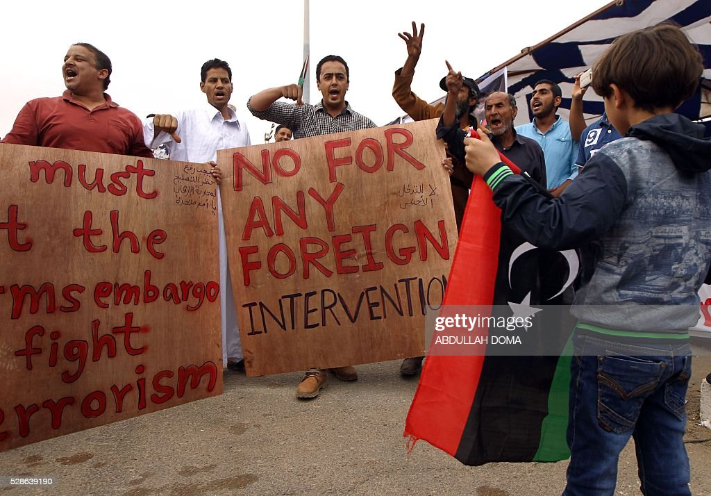 Libyans hold banners as they take part demonstration in the eastern coastal city of Benghazi calling for military forces to re-capture the southern city of Sirte from the Islamic State (IS) group without foreign intervention on May 6, 2016. The head of Libya's unity government announced plans the previous month for a concerted campaign to drive the Islamic State group out of the North African country, but without foreign intervention. The unity government fears that separate operations in Sirte could spark clashes between the multitude of different fighting forces in Libya and play into the jihadists' hands. DOMA