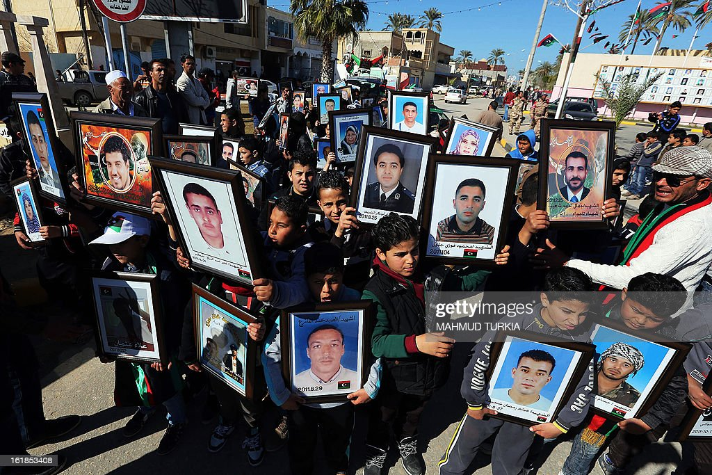 Libyans hold portraits of victims killed in the uprising during events marking the second anniversary of the Libyan revolution on February 17, 2013, in Tripoli. Security forces were on high alert across Libya as the North African nation marked two years since the start of the revolt that toppled Moamer Kadhafi after four decades of iron rule.