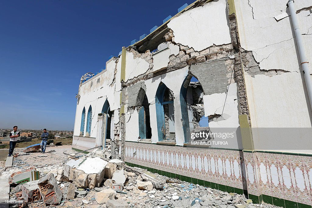 Libyans inspect the damage at a Sufi shrine in the neighbourhood of Tajoura, on the outskirts of Tripoli, after is was attacked during the early hours of the morning by unknown individuals on March 28, 2013. Unknown attackers planted and set off an explosive device, partially destroying the mausoleum of Sidi Mohamed Landoulsi, a 15th Century Sufi Theologist. AFP PHOTO/MAHMUD TURKIA