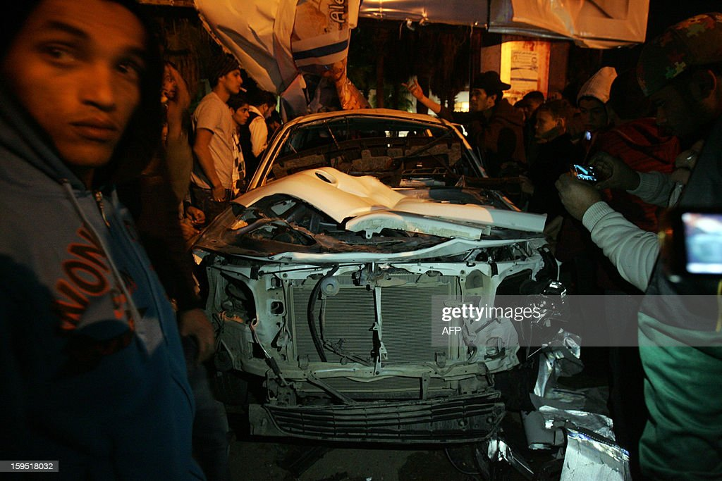 Libyans look at a destroyed car after an improvised bomb hit a police patrol vehicle late on January 14, 2013 in a central neighbourhood of the eastern city of Benghazi. The blast comes two days after the Italian consul to Benghazi, Guido De Sanctis, escaped a gun attack unscathed while inside his armoured vehicle in the Mediterranean city.