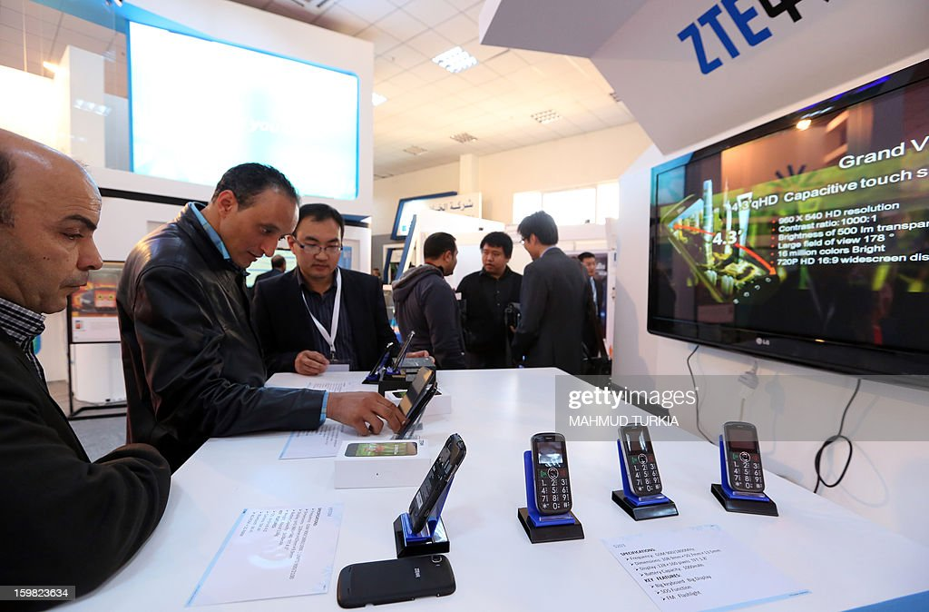 Libyans look at telephones during the opening of the seventh annual exhibition for Communications and Information Technology in the Libyan capital Tripoli, on January 21, 2013.
