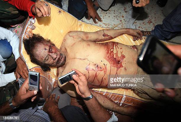 CONTENT Libyans take pictures with their mobile phones of the body of Moamer Kadhafi in Misrata on October 20 2011 The veteran strongman was killed...