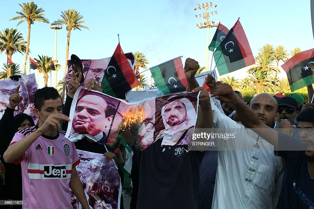 Image result for Libyans wave their national flag and burn portraits of Egyptian President Abdel Fattah al-Sisi (L) and the ruler of Dubai Shiekh Mohamed Bin Rashid al-Maktoum during a protest in Tripoli Martyrs' Square against French military...More