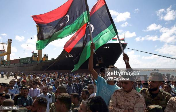 Libyans wave their national flag at the Benghazi port which was closed for the past three years due to rebel groups occupying the eastern Libyan city...