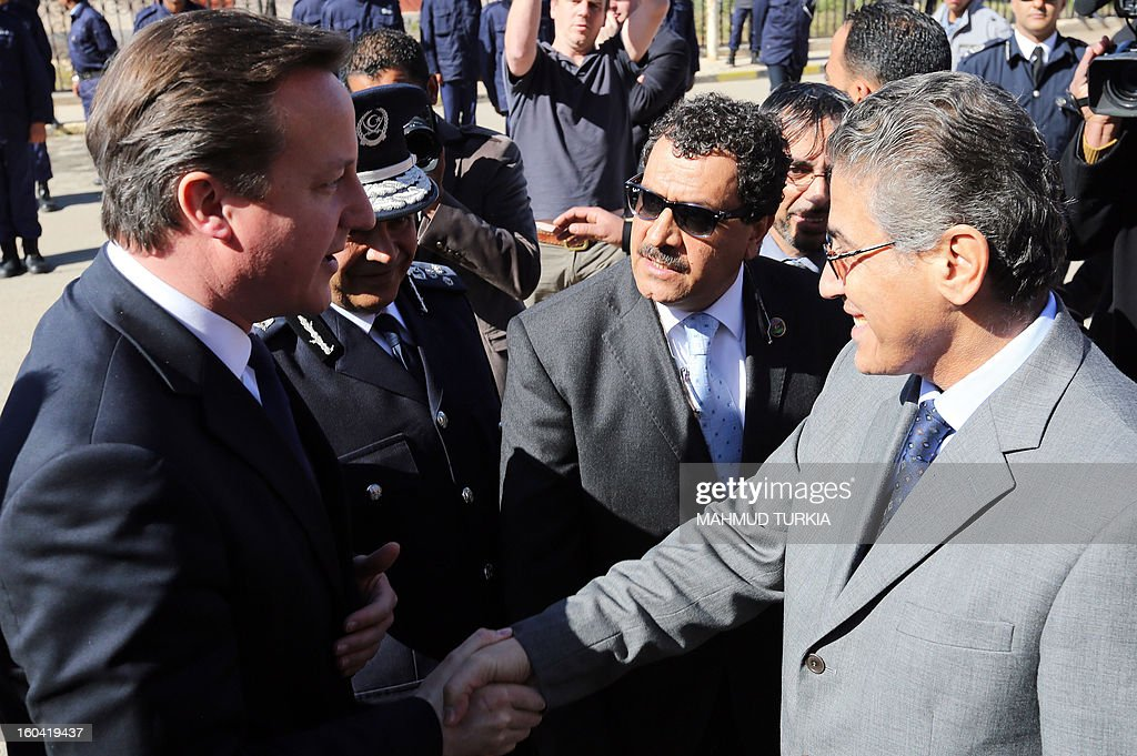 Libya's Interior Minister Ashour Shuail (L) greets British Prime Minister David Cameron (R) upon his arrival to attend a graduation ceremony for Police Officers as part of a visit in Libya on January 31, 2013 in Tripoli. Cameron does a surprise visit in Libya following a one-day-visit in Algeria in the wake of this month's hostage crisis in the Sahara in which several Britons were killed.