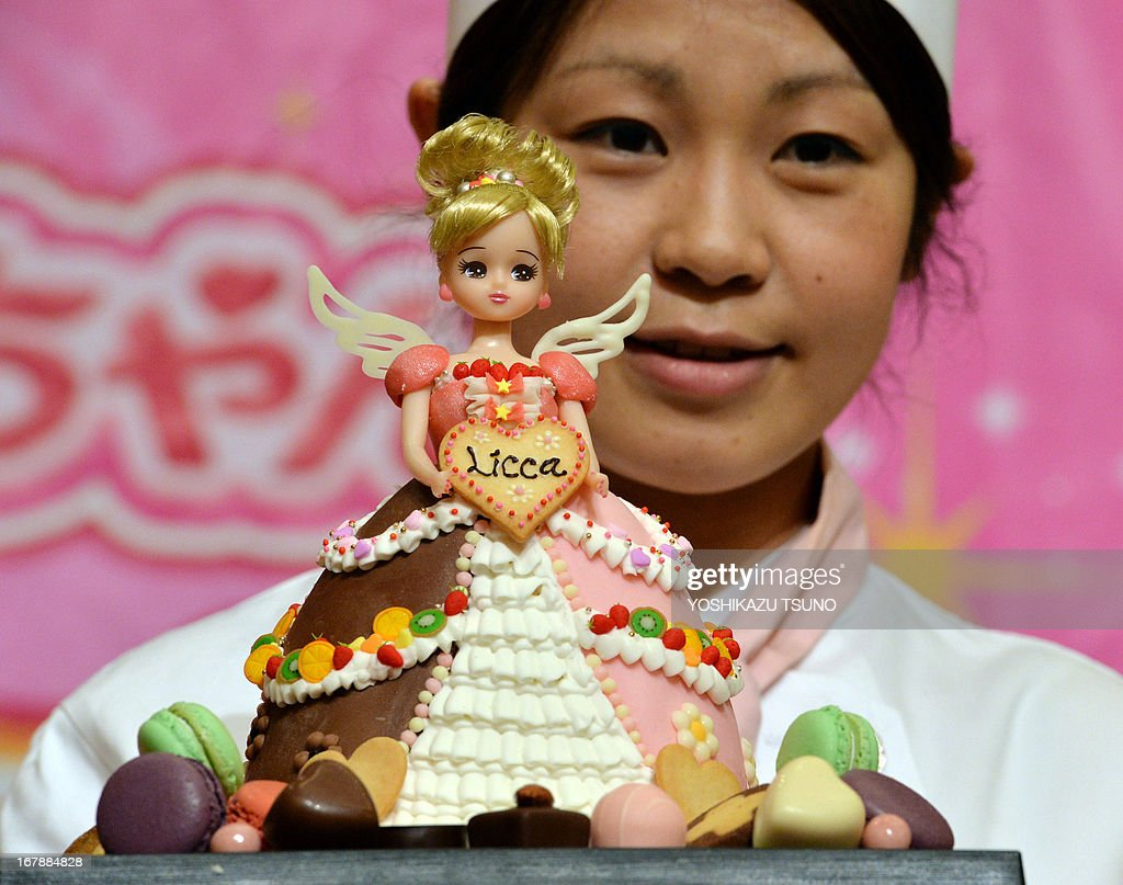 A Licca-chan doll, from a popular dress-up doll series, wearing a 'Sweetie dress Licca-chan' cake dress made by hotel patissier Masako Nobe (back) is displayed at a press preview at Tokyo's Prince hotel on May 2, 2013, before events to celebrate the doll's birthday on May 3 and Children's Day on May 5. Nobe made an original dressed Licca-chan doll and four more dressed dolls wearing lookalike cake dresses of the toy maker's latest dress collection. AFP PHOTO / Yoshikazu TSUNO