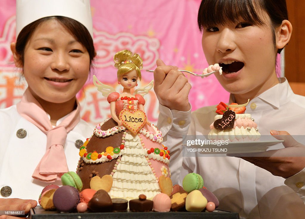 A Licca-chan doll, from a popular dress-up doll series, wearing a 'Sweetie dress Licca-chan' cake dress made by hotel patissier Masako Nobe (L) is displayed at a press preview at Tokyo's Prince hotel on May 2, 2013, before events to celebrate the doll's birthday on May 3 and Children's Day on May 5. Nobe made an original dressed Licca-chan doll and four more dressed dolls wearing lookalike cake dresses of the toy maker's latest dress collection. AFP PHOTO / Yoshikazu TSUNO