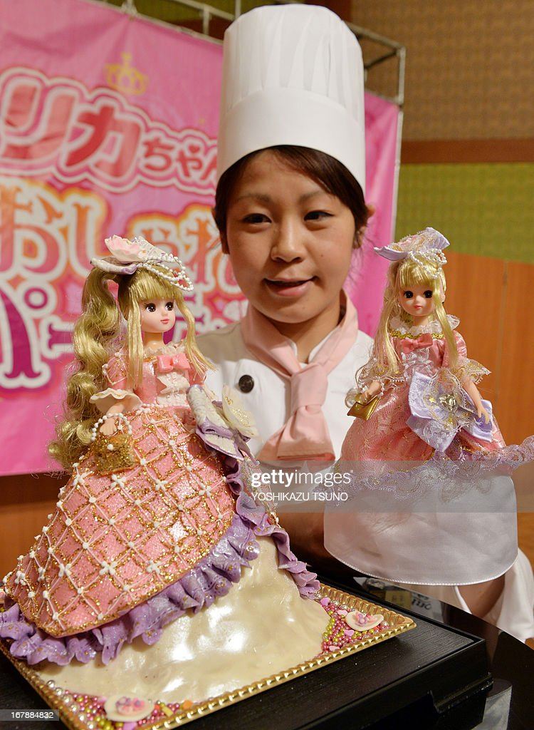 Licca-chan dolls, from a popular dress-up doll series, wearing a 'Sweetie dress Licca-chan' cake dress made by hotel patissier Masako Nobe (back) is displayed at a press preview at Tokyo's Prince hotel on May 2, 2013, before events to celebrate the doll's birthday on May 3 and Children's Day on May 5. Nobe made an original dressed Licca-chan doll and four more dressed dolls wearing lookalike cake dresses of the toy maker's latest dress collection. AFP PHOTO / Yoshikazu TSUNO