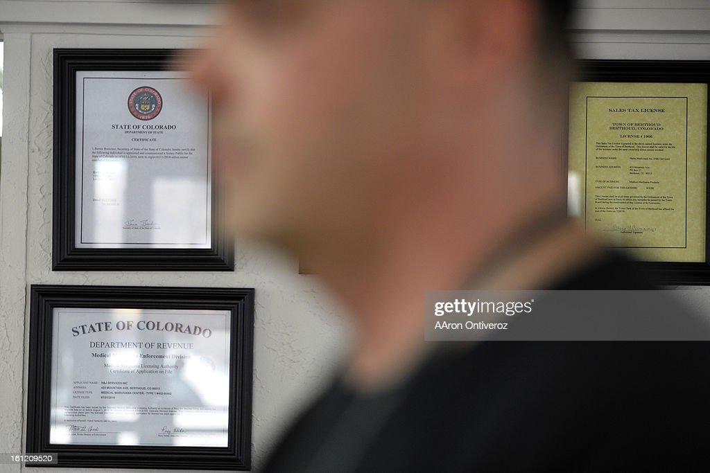 MMJ licenses hang on a wall behind Kevin Ballinger at his medical marijuana shop, Herb's Medicinals, in Berthoud on Thursday, February 23, 2012. AAron Ontiveroz, The Denver Post